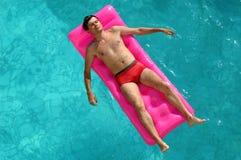 Homem novo que flutua em um colchão na associação de água Fotografia de Stock Royalty Free