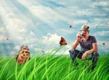 Homem novo que fotografa borboletas na câmera no prado Imagens de Stock Royalty Free