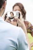 Homem novo que fotografa a mulher através da câmara digital no parque imagem de stock