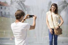 Homem novo que fotografa a mulher contra a fonte Fotografia de Stock
