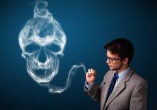 Homem novo que fuma o cigarro perigoso com fumo tóxico do crânio Imagem de Stock Royalty Free