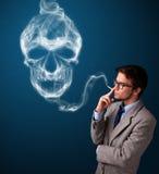 Homem novo que fuma o cigarro perigoso com fumo tóxico do crânio foto de stock
