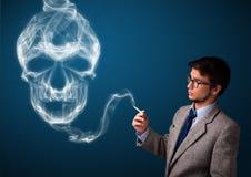 Homem novo que fuma o cigarro perigoso com fumo tóxico do crânio Fotografia de Stock