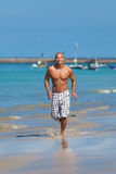 Homem novo que funciona na praia Imagens de Stock