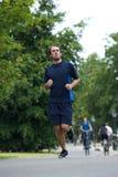 Homem novo que funciona no parque Foto de Stock Royalty Free