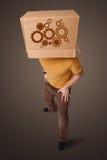 Homem novo que gesticula com uma caixa de cartão em sua cabeça com dente reto w Imagens de Stock