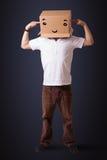Homem novo que gesticula com uma caixa de cartão em sua cabeça com smiley Imagens de Stock Royalty Free