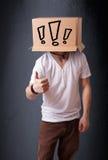 Homem novo que gesticula com uma caixa de cartão em sua cabeça com exclam Foto de Stock