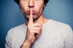 Homem novo que gesticula o silêncio com o dedo nos bordos Imagem de Stock Royalty Free