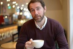 Homem novo que guarda a caneca de café na cafetaria imagem de stock royalty free
