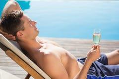 Homem novo que guarda a flauta de champanhe pela piscina Fotos de Stock Royalty Free