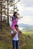 Homem novo que guarda a menina em um pescoço Imagens de Stock