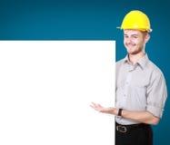 Homem novo que guarda o capacete de segurança vestindo do quadro de avisos vazio Fotografia de Stock Royalty Free