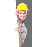 Homem novo que guarda o capacete de segurança vestindo do quadro de avisos vazio Fotografia de Stock