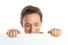 Homem novo que guarda o cartaz vazio fotos de stock royalty free