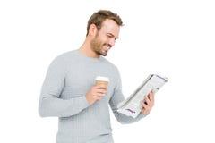 Homem novo que guarda o copo descartável e que lê o jornal fotos de stock