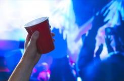 Homem novo que guarda o copo vermelho do partido no salão de baile do clube noturno Recipiente do álcool à disposição no disco Imagens de Stock Royalty Free
