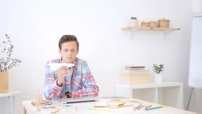 Homem novo que guarda o plano de papel, pensando uma ideia Fotografia de Stock Royalty Free