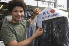 Homem novo que guarda o recibo na loja da tinturaria Imagem de Stock