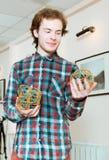 Homem novo que guarda os modelos volumétricos de sólidos geométricos imagens de stock