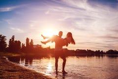Homem novo que guarda sua amiga em suas mãos Acople ter o divertimento no banco de rio do verão no por do sol Indivíduos que rela Imagens de Stock