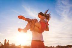 Homem novo que guarda sua amiga em suas mãos Acople ter o divertimento no parque do verão no por do sol Riso dos indivíduos Foto de Stock