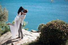 Homem novo que guarda sua mulher moreno 'sexy' nos braços, eles que beijam Estão estando em um seascape bonito perto do mar fotografia de stock