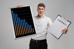Homem novo que guarda um cartaz com estatísticas e o contrato isolado em um fundo claro fotografia de stock