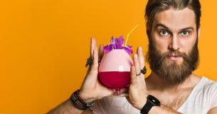 Homem novo que guarda um cocktail colorido imagem de stock