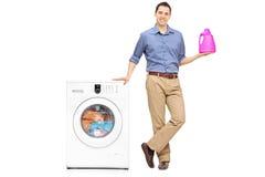 Homem novo que guarda um detergente para a roupa fotografia de stock royalty free