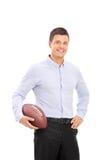Homem novo que guarda um futebol americano Fotografia de Stock Royalty Free