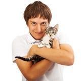 Homem novo que guarda um gatinho pequeno imagem de stock