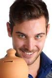 Homem novo que guarda um moneybox da argila Imagem de Stock Royalty Free