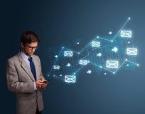 Homem novo que guarda um telefone com setas e ícones da mensagem Fotos de Stock Royalty Free