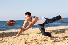 Homem novo que guarda uma bola de rugby Imagens de Stock