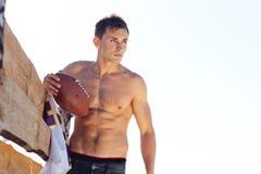 Homem novo que guarda uma bola de rugby Imagem de Stock Royalty Free