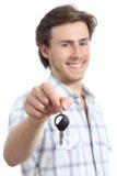 Homem novo que guarda uma chave do carro alugado Fotografia de Stock Royalty Free