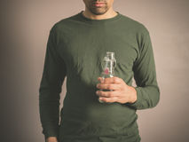 Homem novo que guarda uma garrafa de vidro pequena Imagens de Stock