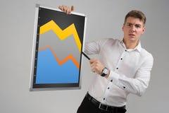 Homem novo que guarda uma placa magnética com um gráfico isolado em um fundo claro imagens de stock
