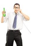 Homem novo que guardara uma cerveja e que fala em um telefone Imagem de Stock