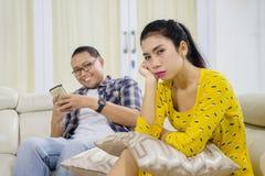 Homem novo que ignora sua esposa em casa Imagens de Stock