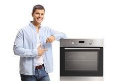 Homem novo que inclina-se em um forno e em apontar foto de stock