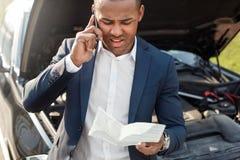 Homem novo que inclina-se no carro com a capa aberta que guarda o seguro que chama o close-up olhando de sobrancelhas franzidas d imagens de stock