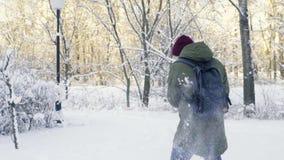 Homem novo que joga bolas de neve no parque filme