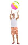 Homem novo que joga com bola de praia imagens de stock