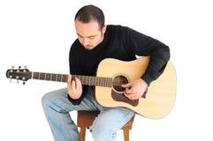 Homem novo que joga a guitarra imagem de stock
