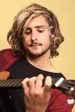 Homem novo que joga a guitarra Fotografia de Stock Royalty Free