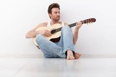 Homem novo que joga a guitarra Imagens de Stock