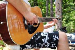 Homem novo que joga a guitarra acústica na natureza imagens de stock royalty free