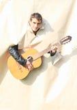Homem novo que joga a guitarra através dos furos Fotos de Stock Royalty Free